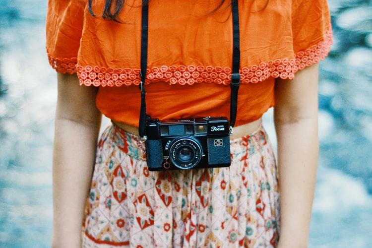 kobieta z aparatem na szyi